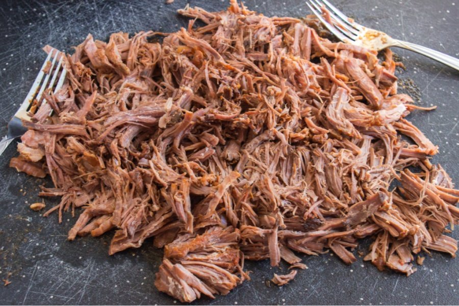 Shredded beef on a cutting board