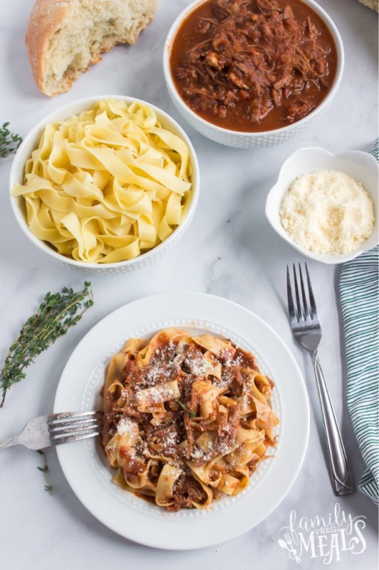 Ragu served on a plate with noodles, and bowls filled with noodles, ragu and shredded cheese