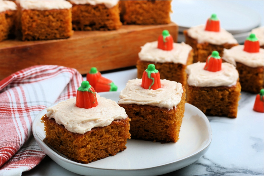 several pumpkin bars on a plate and on a wooden board