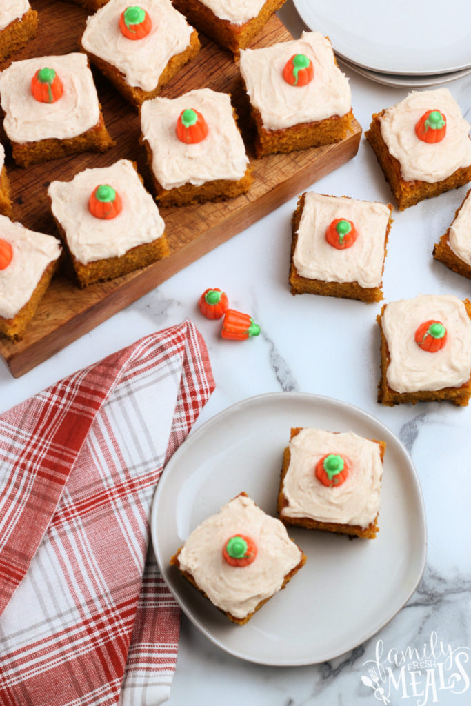 several frosted pumpkin bars on a wooden board and on a plate