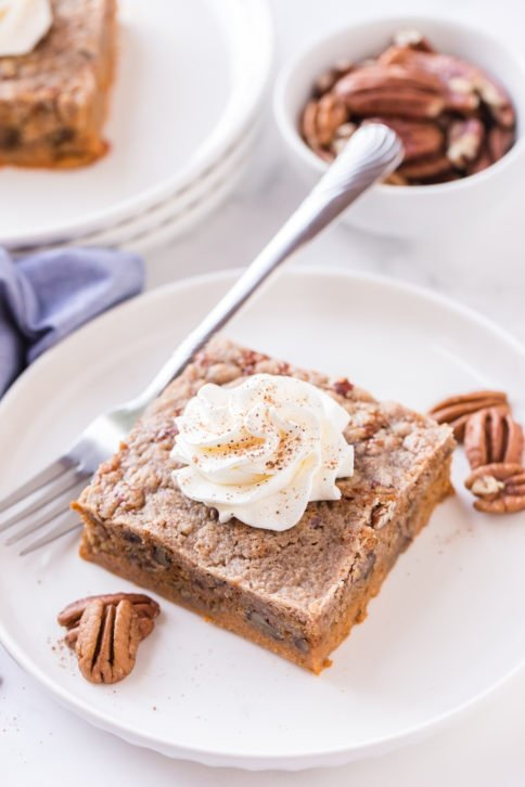 piece of dump cake on a white plate with pecans and whipped cream