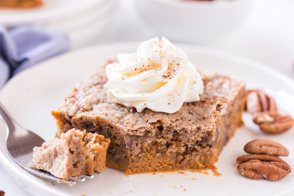 piece of pumpkin dump cake on a white plate, topped with whipped cream