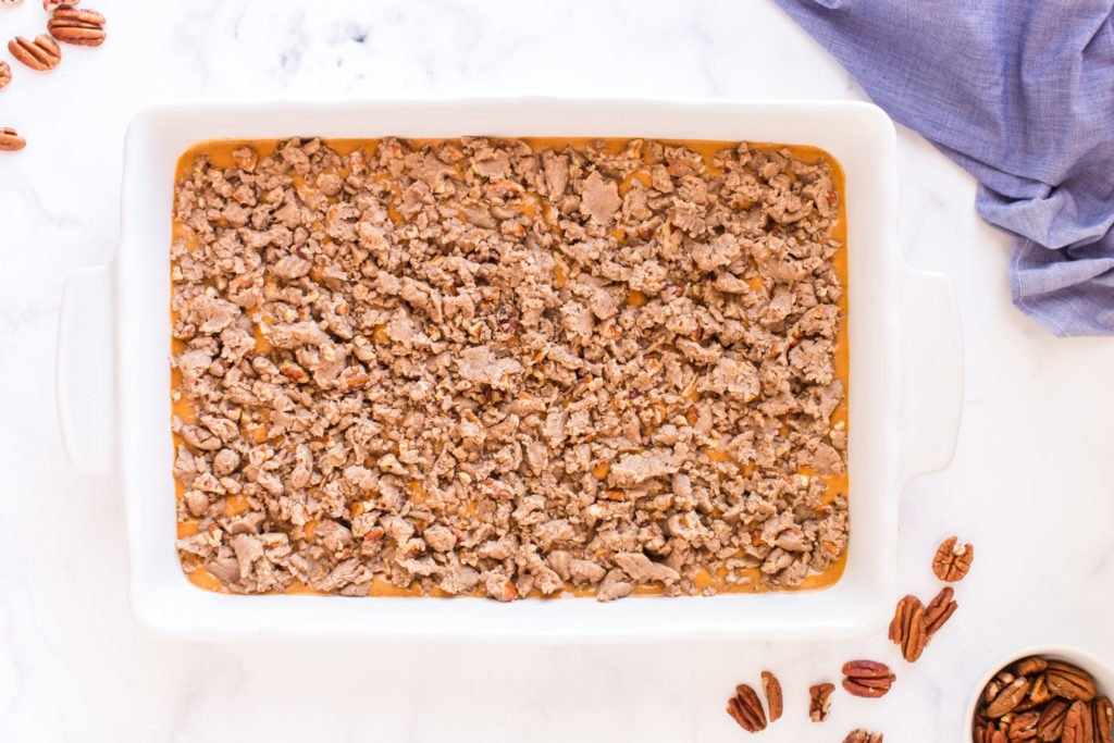 top down image of crumble placed on top of cake before baking