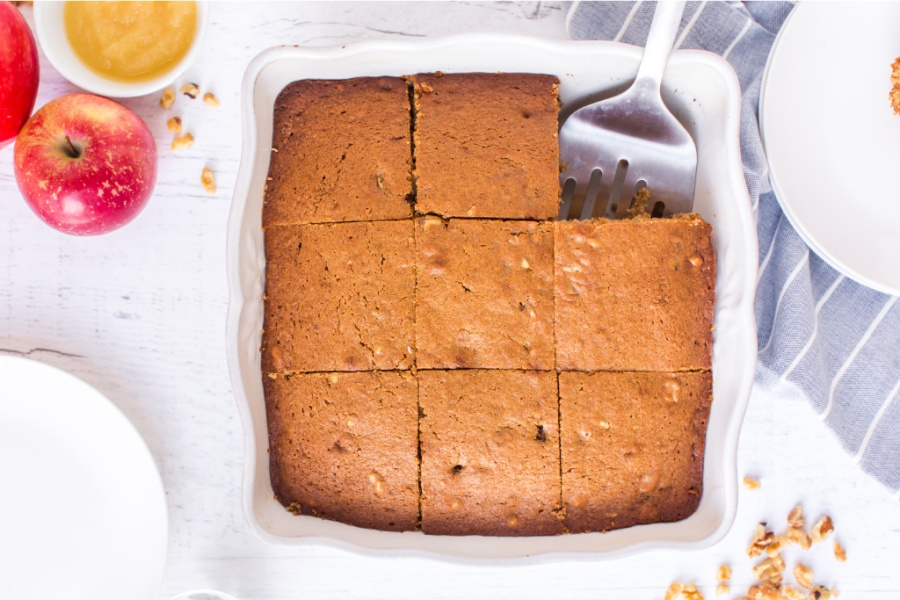 applesauce cake in baking dish with a piece removed
