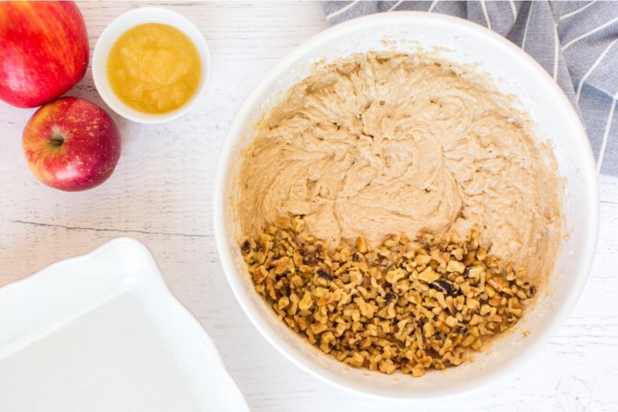 adding walnuts to mixing bowl