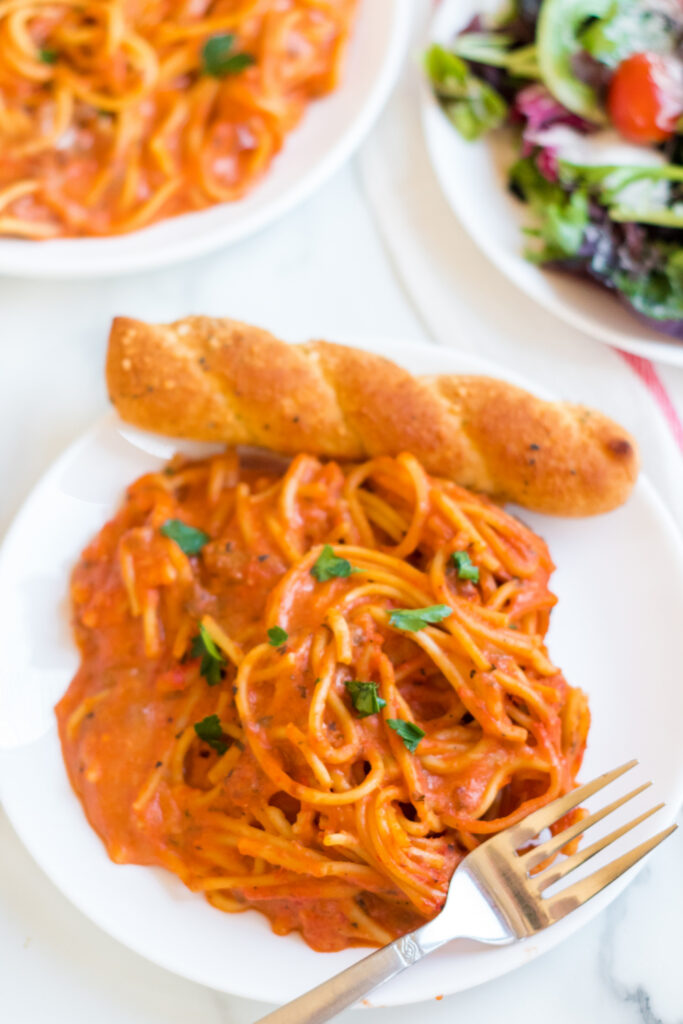 Creamy Crockpot Spaghetti on a plate with a bread stick