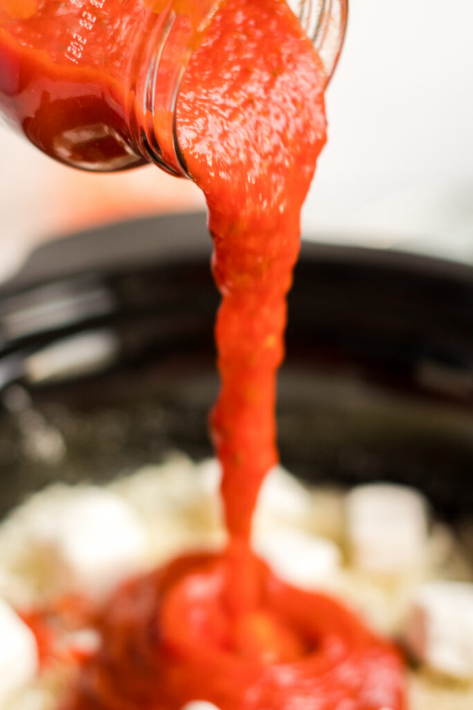 pouring sauce into slow cooker