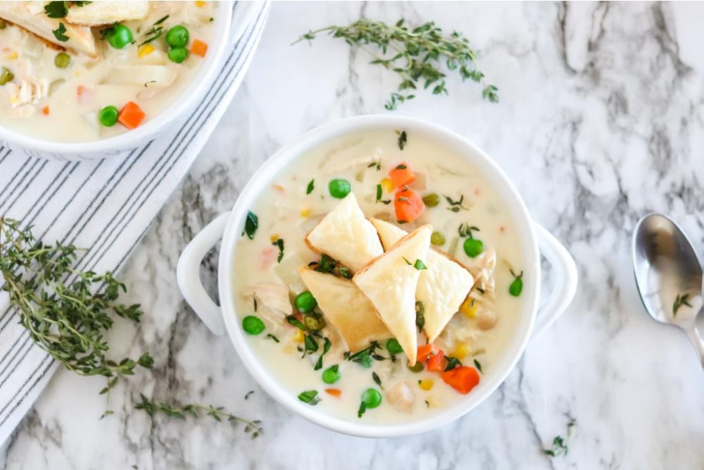 Crockpot Chicken Pot Pie Soupe dans un bol blanc - avec des triangles de pâte feuilletée sur le dessus