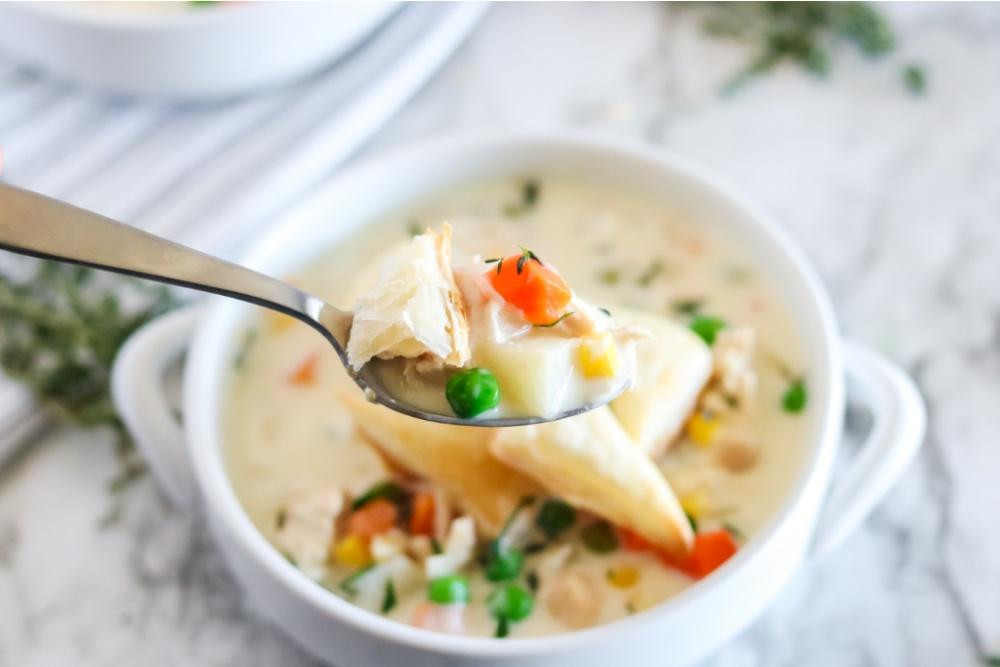 Crockpot Chicken Pot Pie Soupe dans un bol blanc avec une cuillère ramasser certains jusqu'à