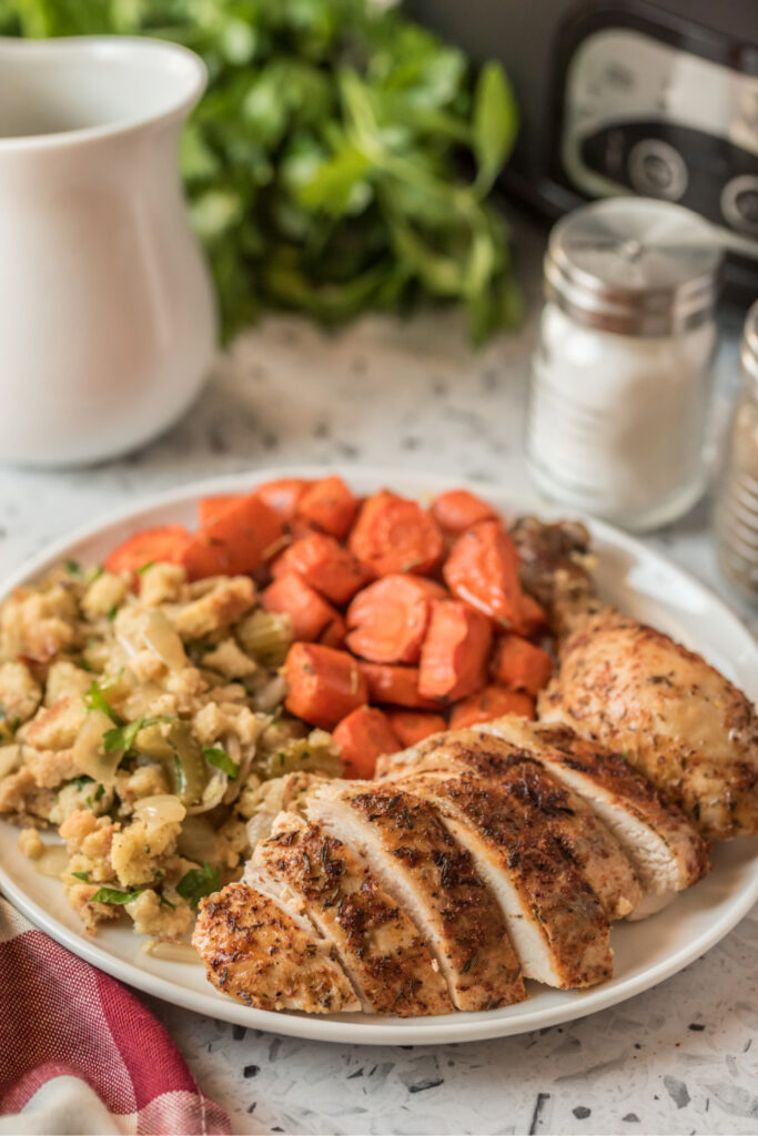 sliced chicken, stuffing and carrots on a plate