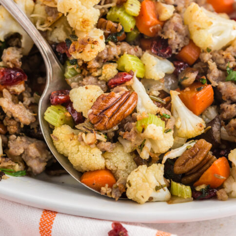Savory cauliflower stuffing on a platter with a serving spoon