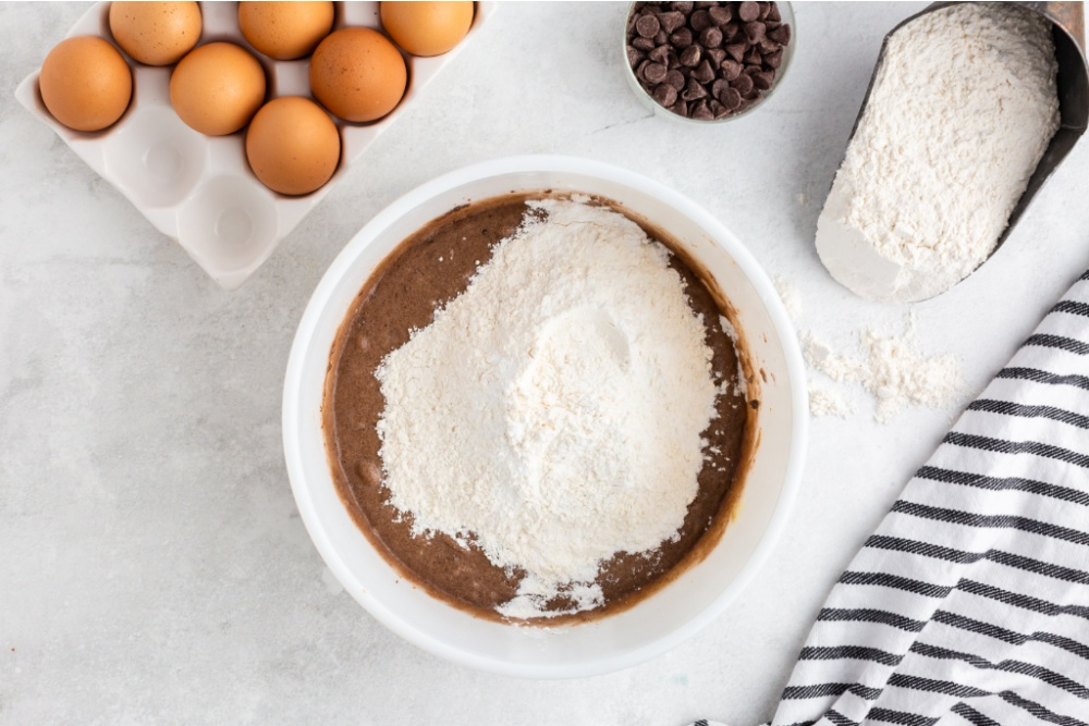 flour and baking soda being added to mixing bowl