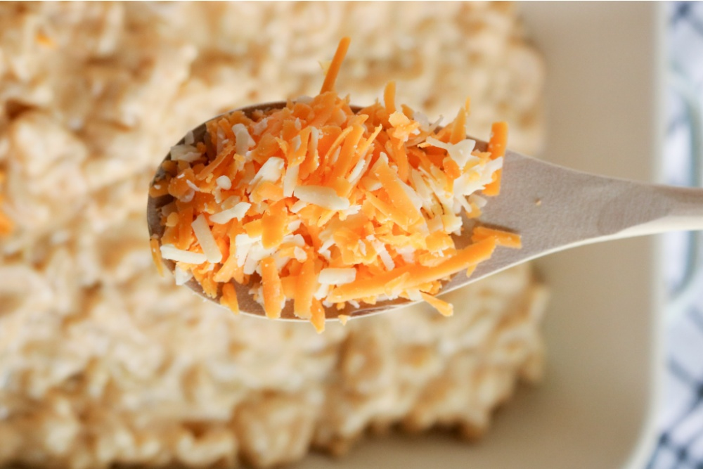 shredded cheese on a wooden spoon, held over casserole dish