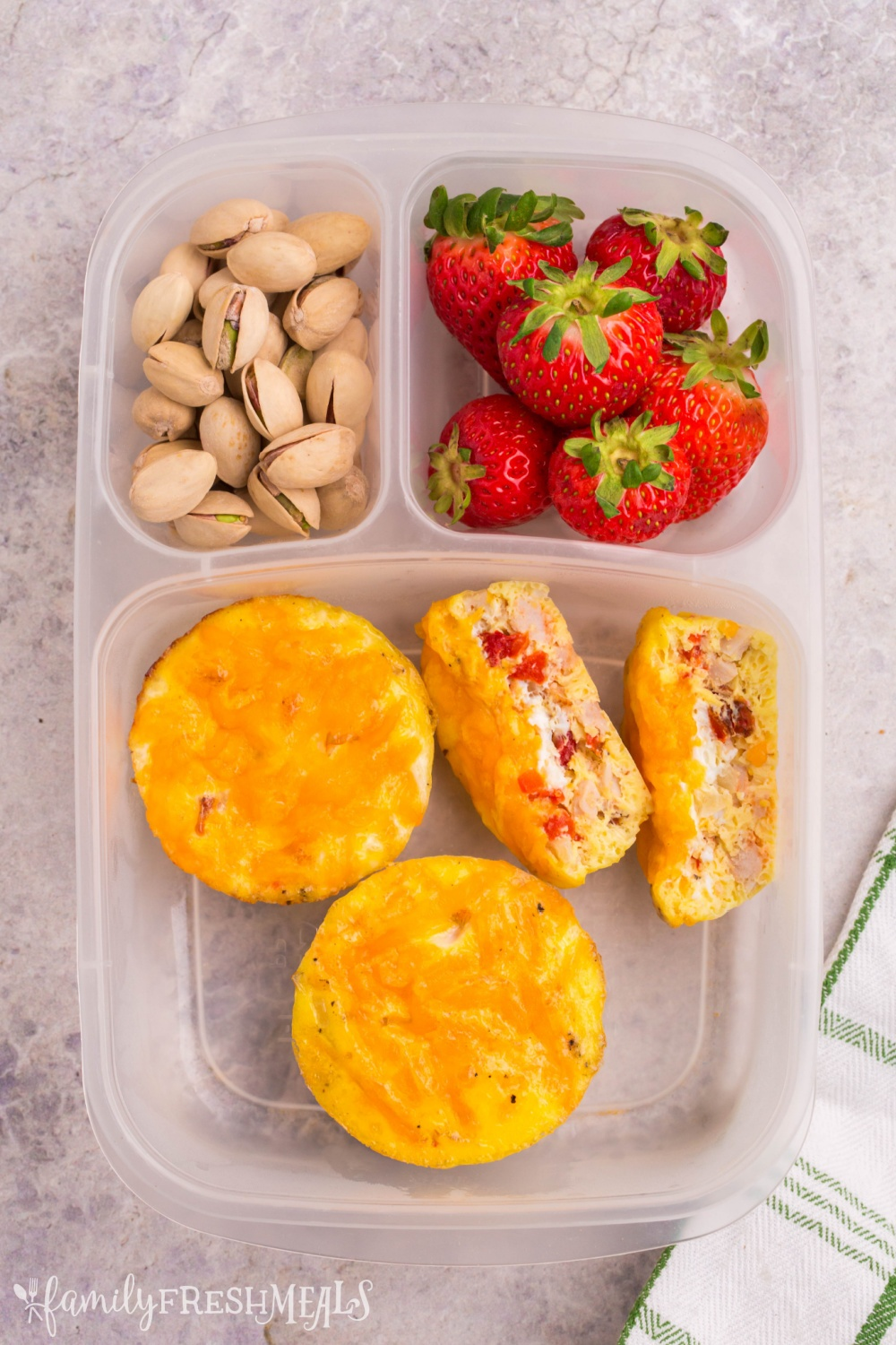 Lunchbox packed with egg cups, strawberries and pistachios