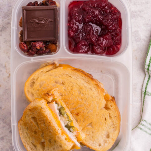 lunchbox packed with green bean casserole grilled cheese, cranberry sauce, nuts and chocolate