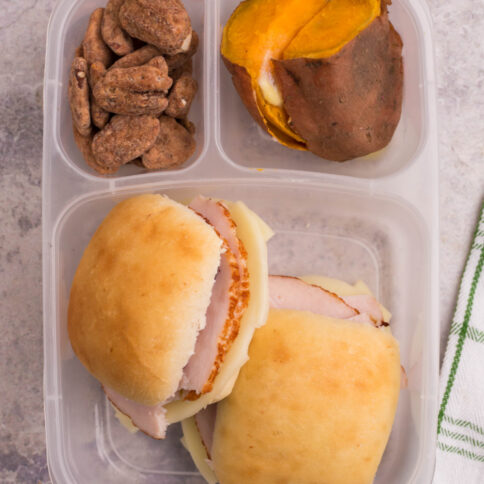 lunchbox packed with 2 mini turkey sliders, sweet potatoes and pecans