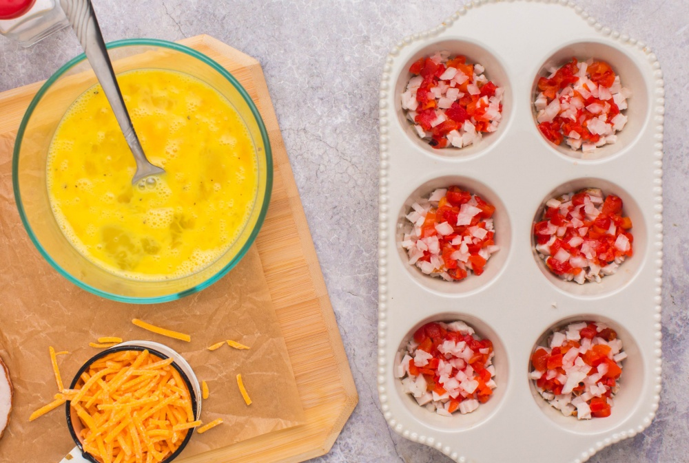 adding chopped onion and peppers into muffin tin