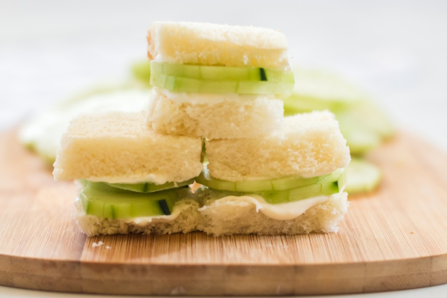 Mini cucumber sandwiches stacked on a cutting board