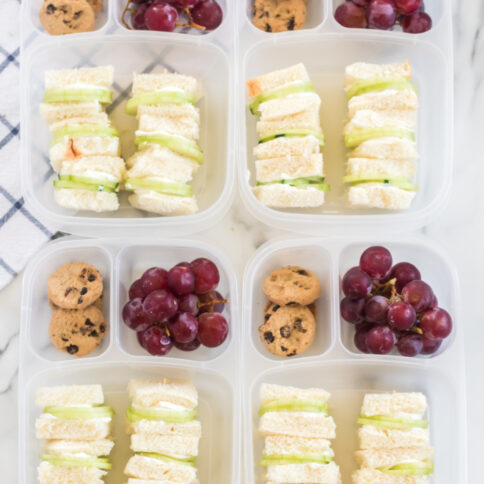 4 lunchboxes packed with Mini Cucumber Sandwiches, cookies and grapes