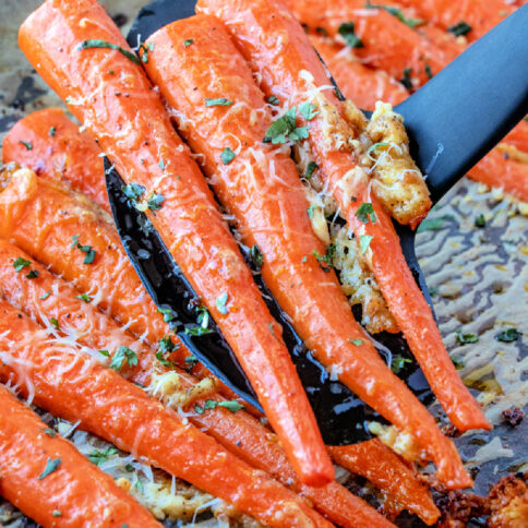 spatula scooping up some roasted carrots off of a baking sheet