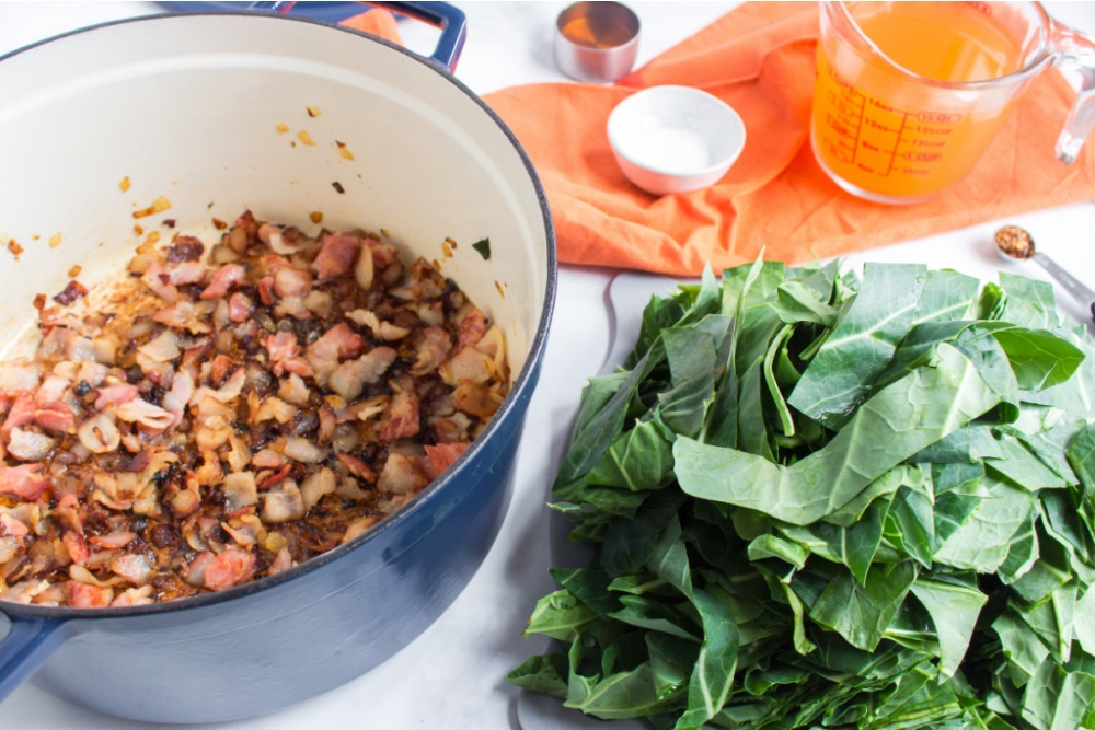 cooked bacon and onion in cooking pot and a pile on greens