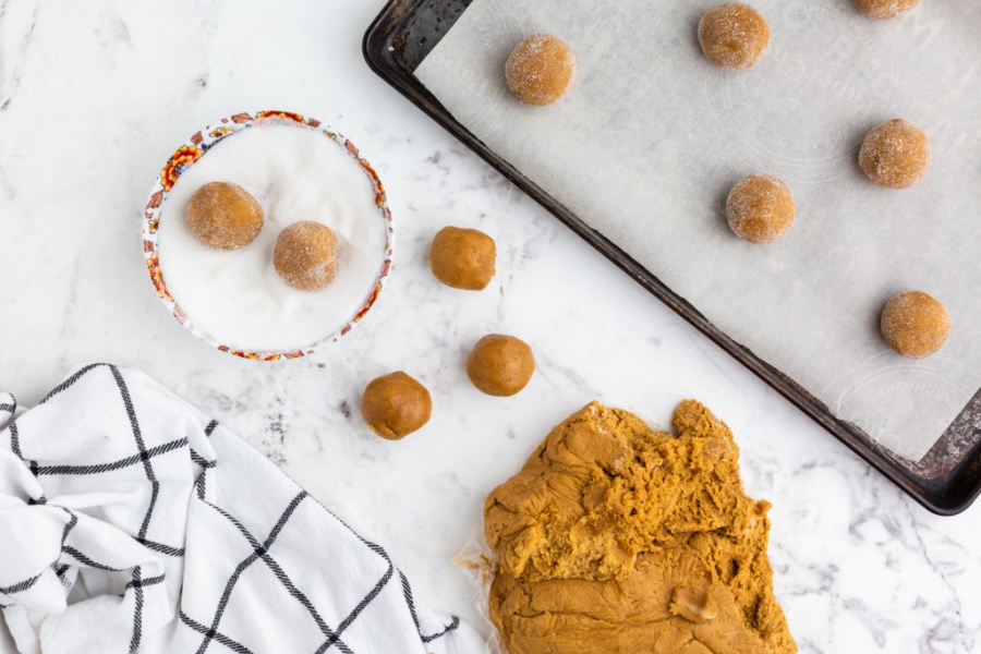 cookie balls being rolled in sugar and placed on baking sheet