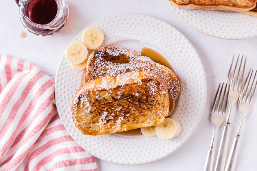 Eggnog French Toast on a plate with sliced bananas