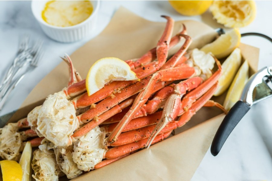 snow crab legs on a serving platter with slices of lemon