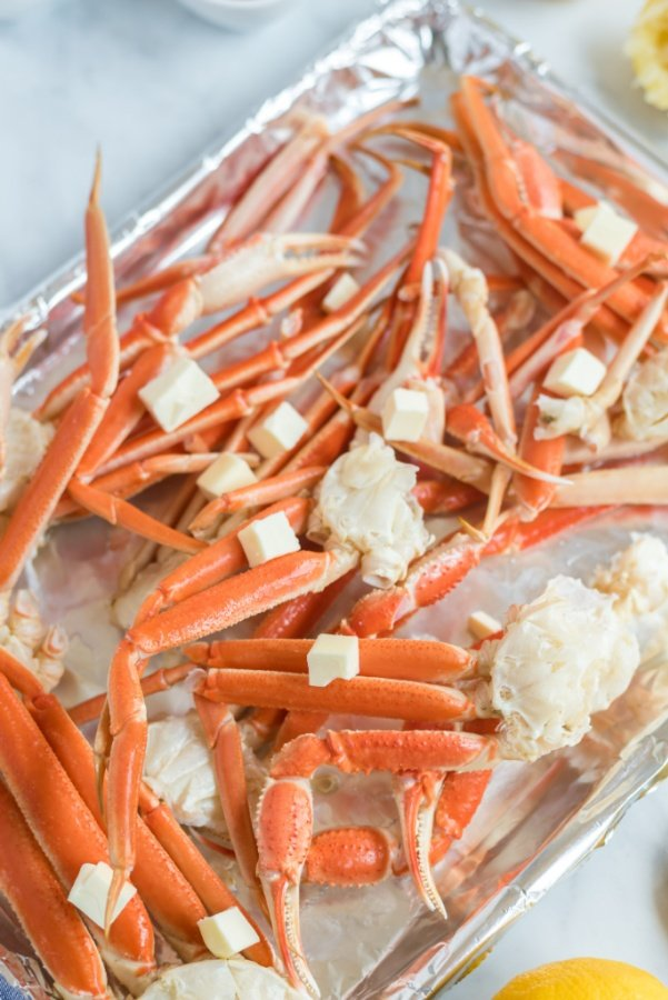crab leg clusters on a baking sheet with butter tabs