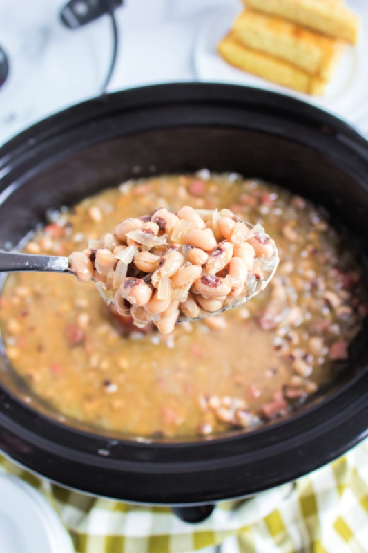 a spoon scooping up black eye peas from a crockpot