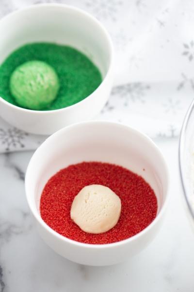 cookie balls being rolled in colored sugar sprinkles