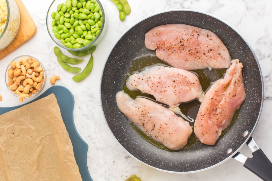 chicken breast cooking in a frying pan