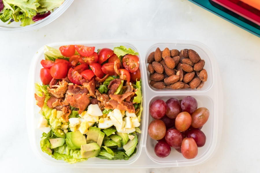 top down picture of lunchbox packed with cobb salad, grapes and almonds