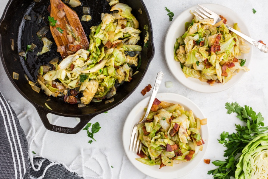 Fried cabbage and bacon in a cast iron pan and on 2 white plates