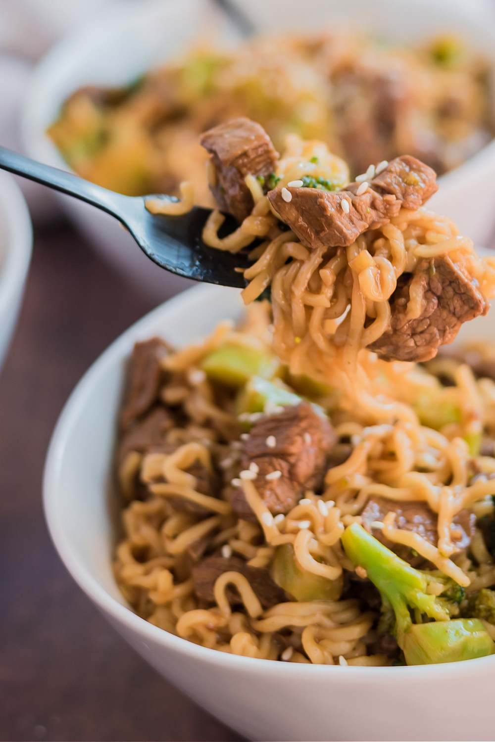 Take-Out Beef and Broccoli Ramen Noodles in two bowls with a fork picking up some