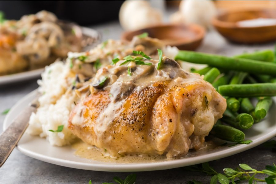 Chicken thighs served with rice and green beans on a plate