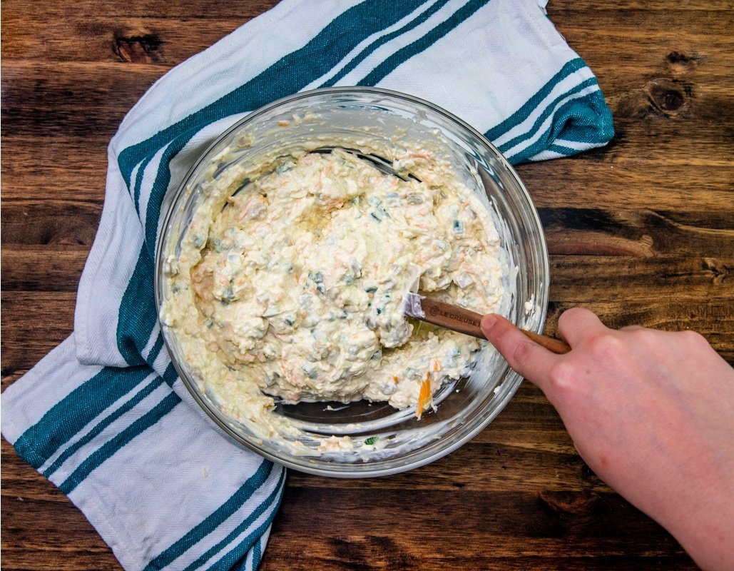 cream cheese, mayonnaise, green chili & jalapeno peppers, cheddar cheese and Monterey Jack cheese being mixed in a mixing bowl