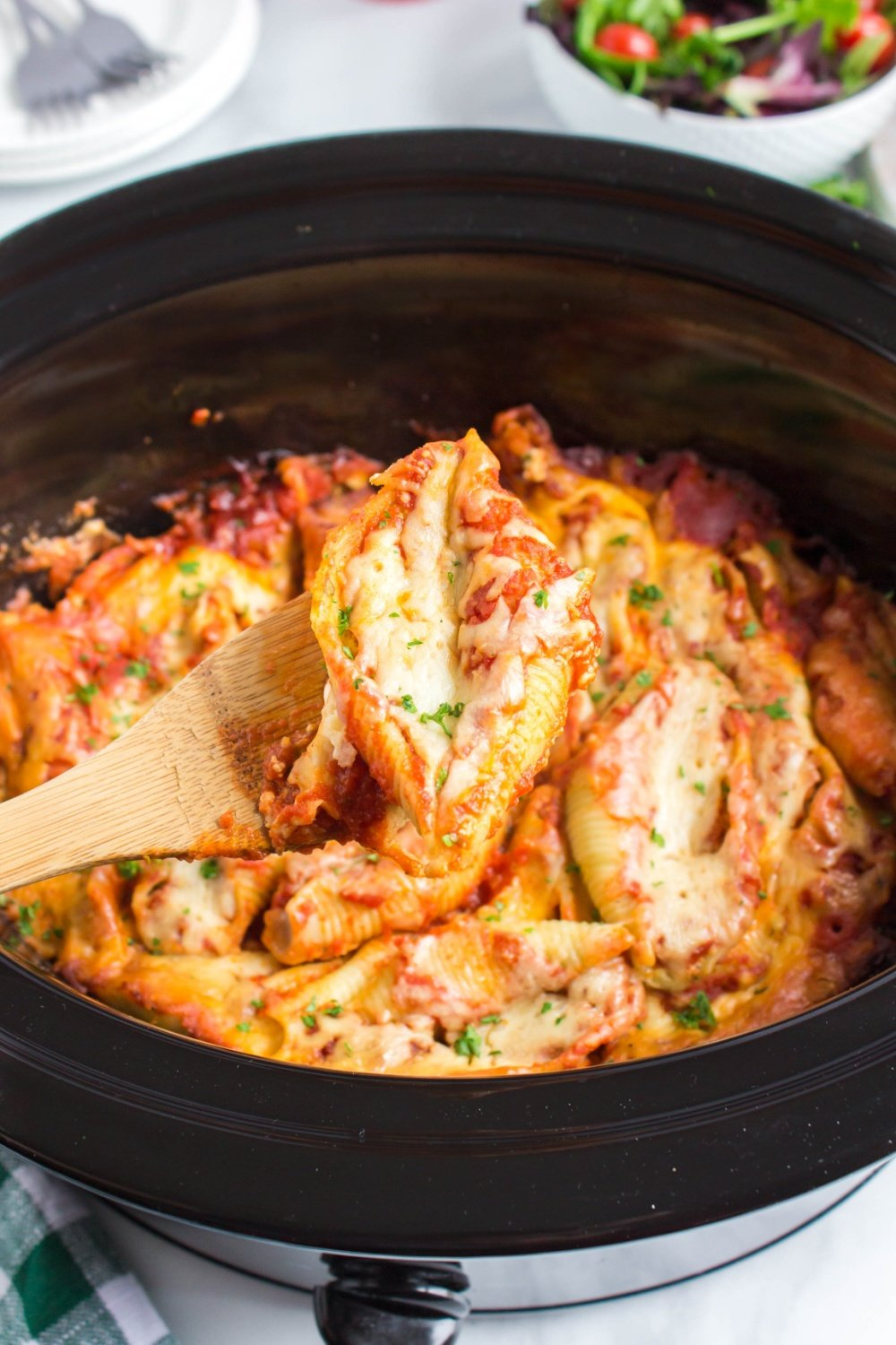 Crockpot Stuffed Shells in a slow cooker with a wooden spoon scooping up a serving