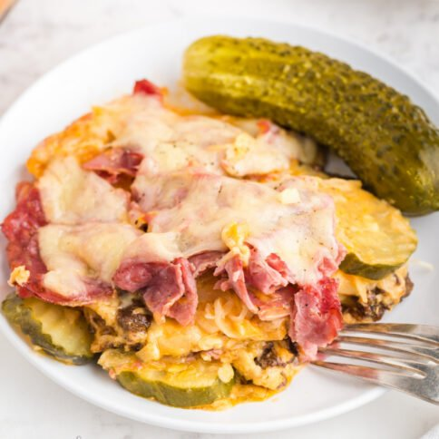 piece of reuben casserole on a plate with a pickle