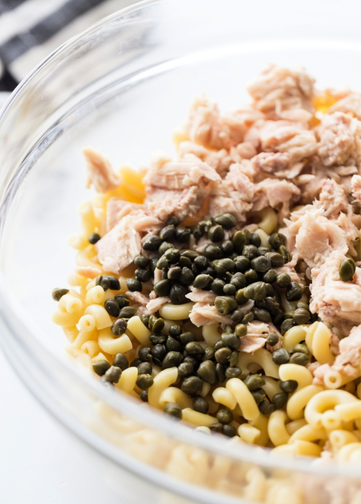 cooked noodles, capers and tuna in a mixing bowl