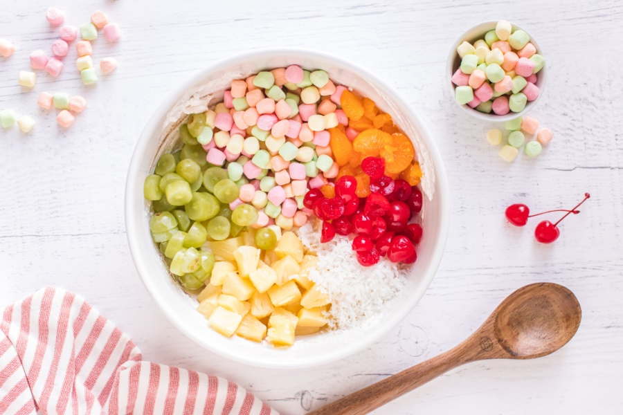 Marshmallows, pineapple, mandarin oranges, cherries, grapes, and coconut added to mixing bowl