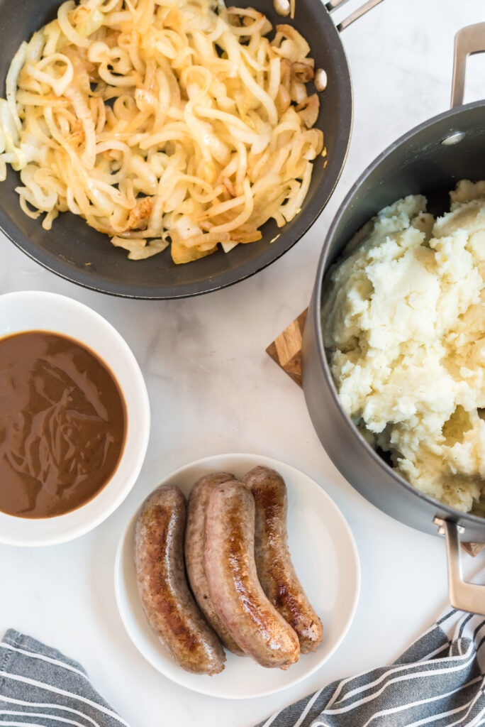 sliced onions cooking in pan, cooked sausage on a plate and a pot of mashed potatoes