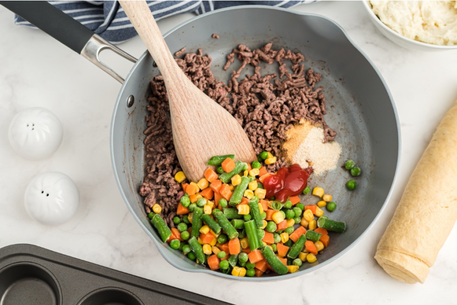 hamburger add garlic, ketchup, Worcestershire sauce, and frozen vegetables in a cooking pan with a wooden spoon stirring