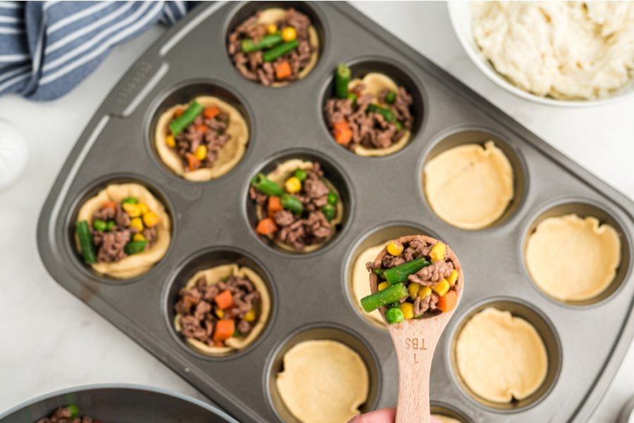 scooping beef mixture into muffin tin