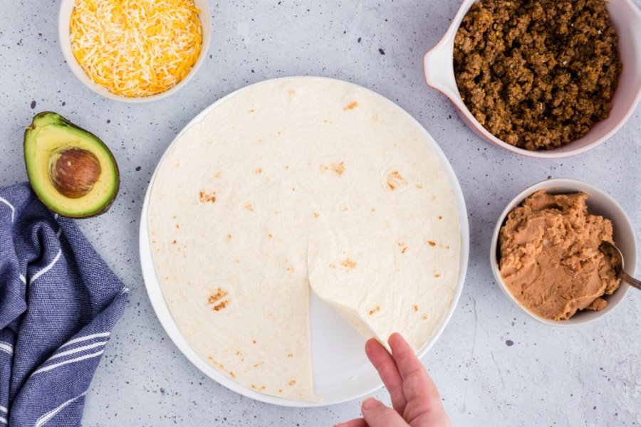hand lifting up section of tortilla