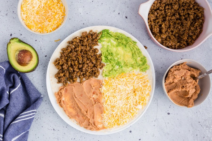 tortilla with beef, avocado, refried beans and cheese on top