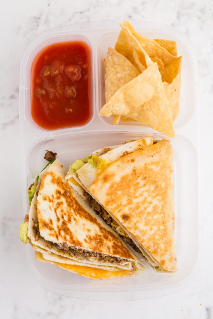 quesadillas packed in a lunchbox container with salsa and chips