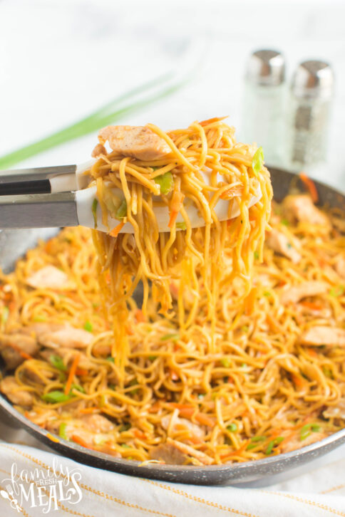 Chicken Chow Mein in a pan with tongs pick up some
