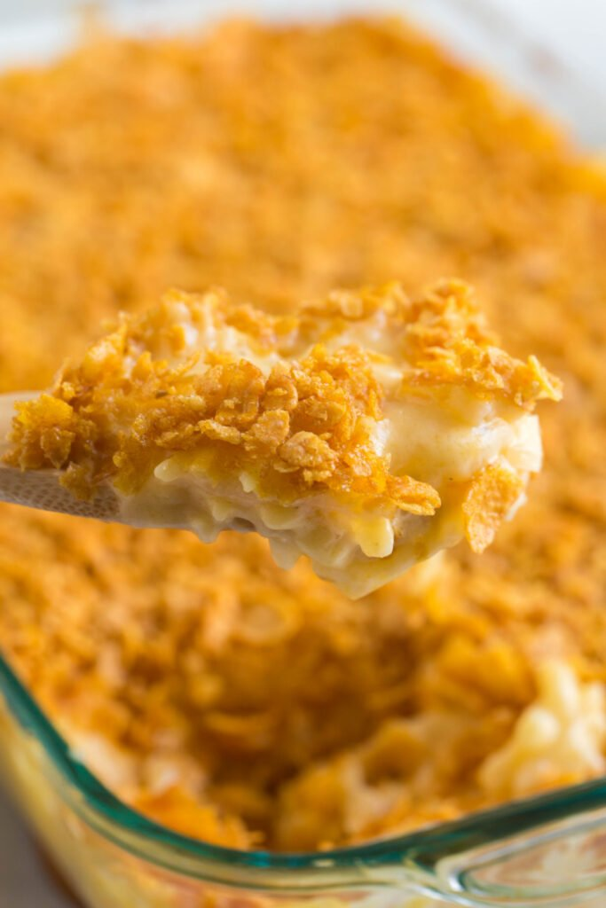 wooden spoon scooping up some Classic Cheesy Funeral Potatoes