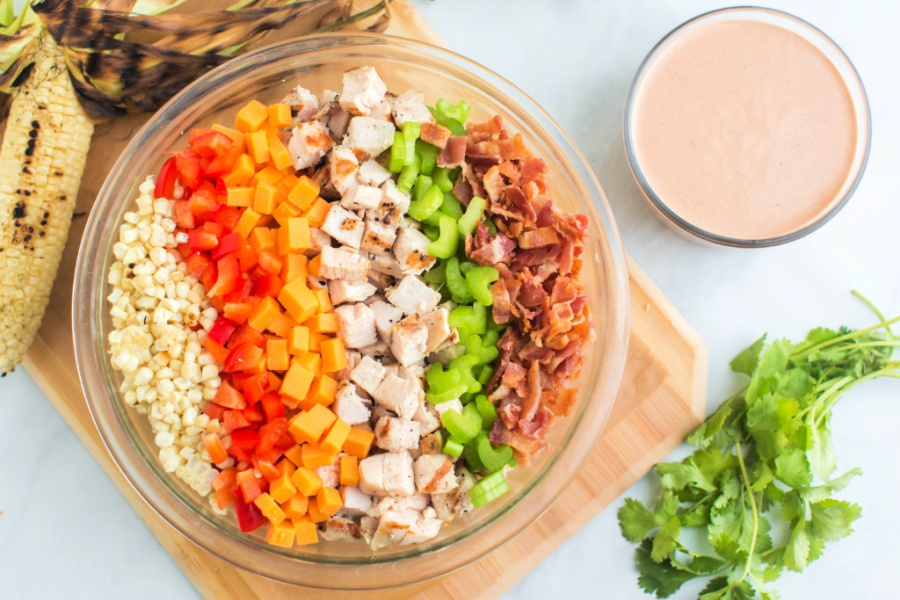 ingredients for bbq chicken pasta salad in a mixing bowl